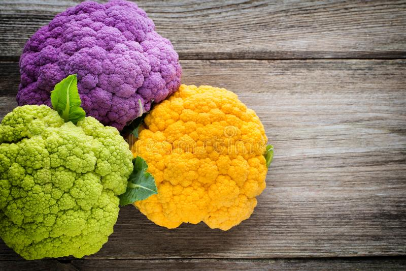 Rainbow of eco cauliflower on the wooden table royalty free stock photography