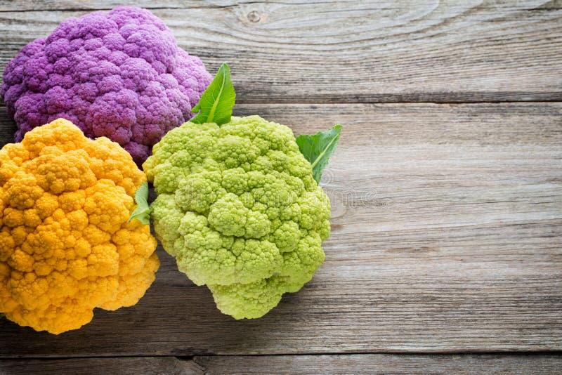 Rainbow of eco cauliflower on the wooden table stock photos