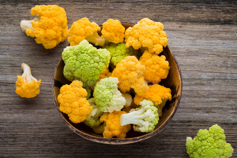 Rainbow of eco cauliflower on the wooden table. royalty free stock photo