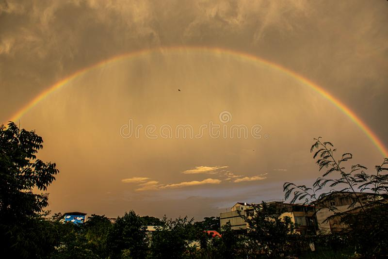 Rainbow enveloped Xinying City. In the evening, the golden light is scattered in the sky, and the semi-circular rainbow covers the Xinying District of Tainan stock photo