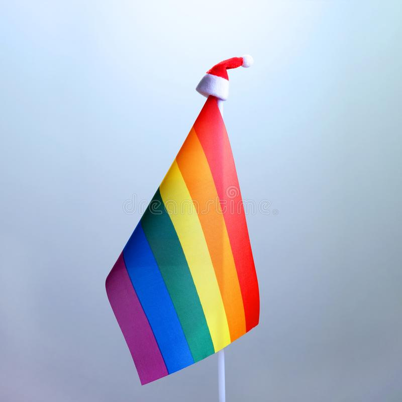 Rainbow flag of sexual minorities with santa claus hat. LGBT representatives and Christmas. Square frame. Concept New Year`s royalty free stock images