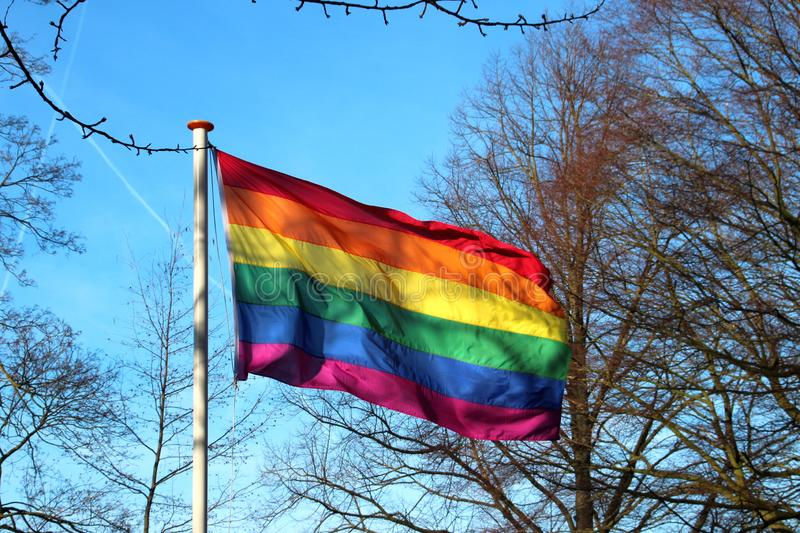 Rainbow flag waving in the wind in the city of Gouda for more respect for LBHTI. In the Netherlands stock photo