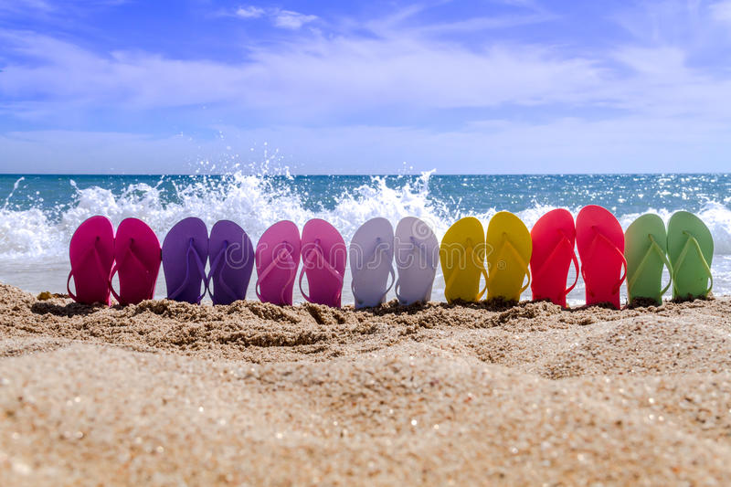 Rainbow Flip Flops. Line of brightly colored flip flops arranged in a rainbow on beach with large waves breaking on sandy shore royalty free stock photography