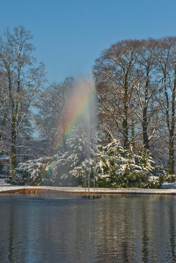 Rainbow fountain in snowy Oranjepark Apeldoorn. Apeldoorn, Netherlands - 2008-11-24 Oranjepark: rainbow fountain in a sunny snowy winter day with the water of stock photography