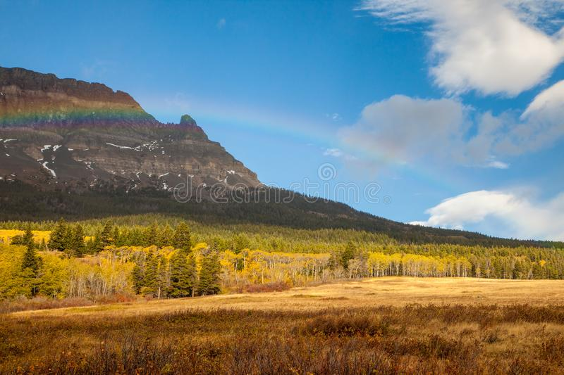 Rainbow on an autumn day in front of a mountain near Saint Mary stock images