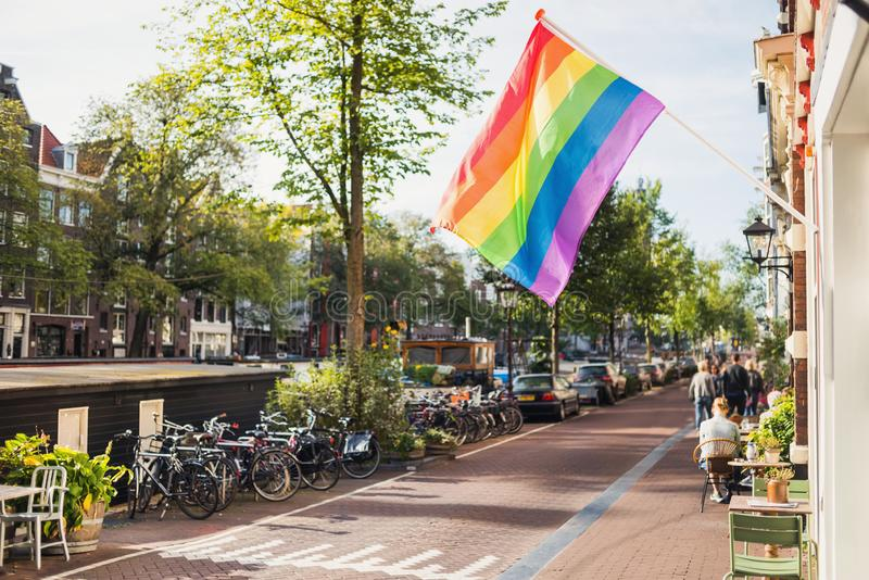 Rainbow gay pride flag in Amsterdam, Netherlands. Popular travel destination in Europe. City life and culture concept stock photo