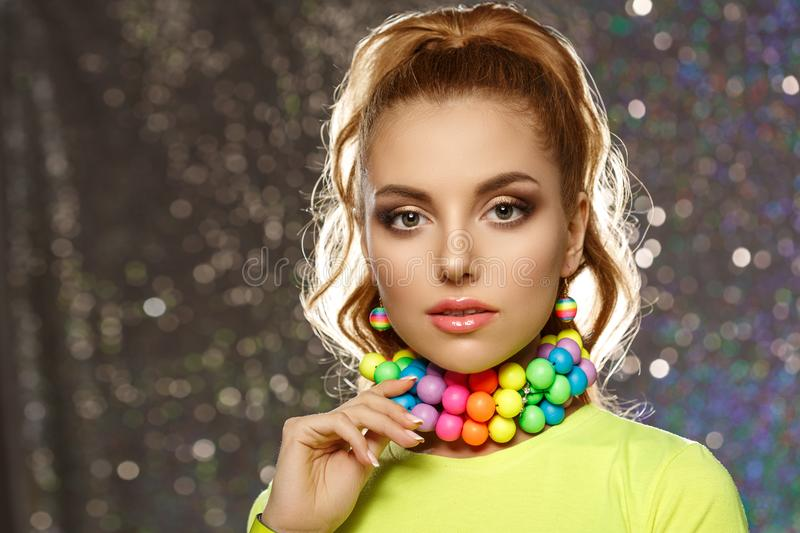 Rainbow girl. Model with colorful bright jewelry. Woman with neat makeup and high hairstyle with colored necklace and earrings stock image