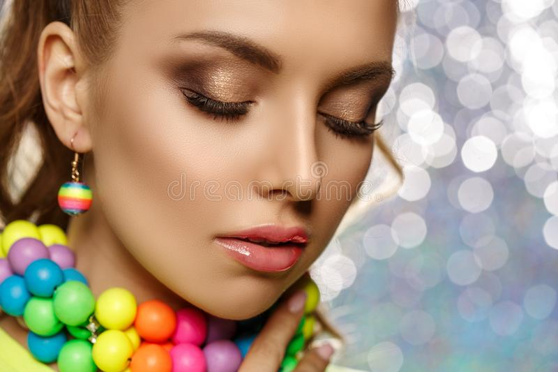 Rainbow girl. Model with colorful bright jewelry. Woman with neat makeup and high hairstyle with colored necklace and earrings royalty free stock photos