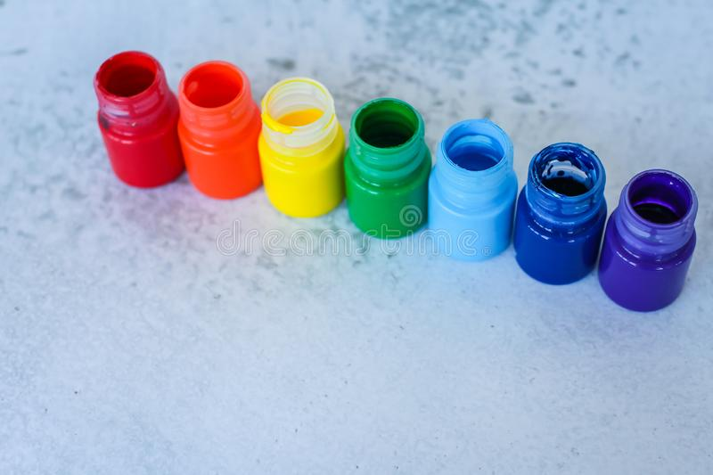 Rainbow Gouache or acrylic paints in jars on white grunge background, selective focus stock photo