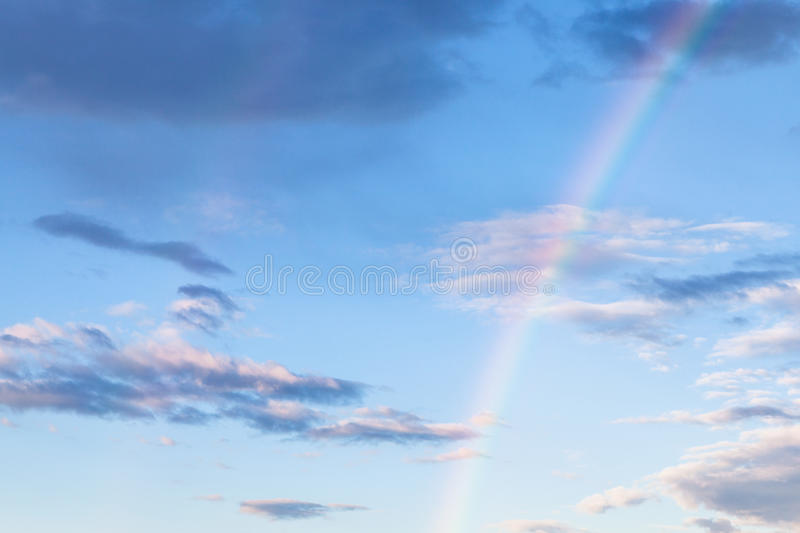 Rainbow and gray clouds in blue evening sky stock photos