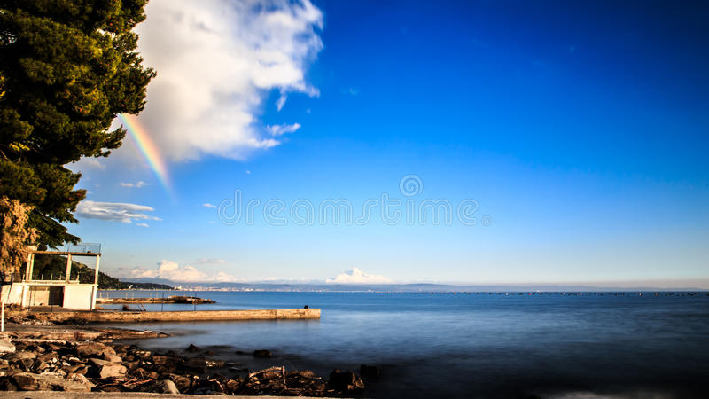 Rainbow in the gulf of Trieste. A spring storm with a colorful rainbow in the gulf of Trieste stock photo
