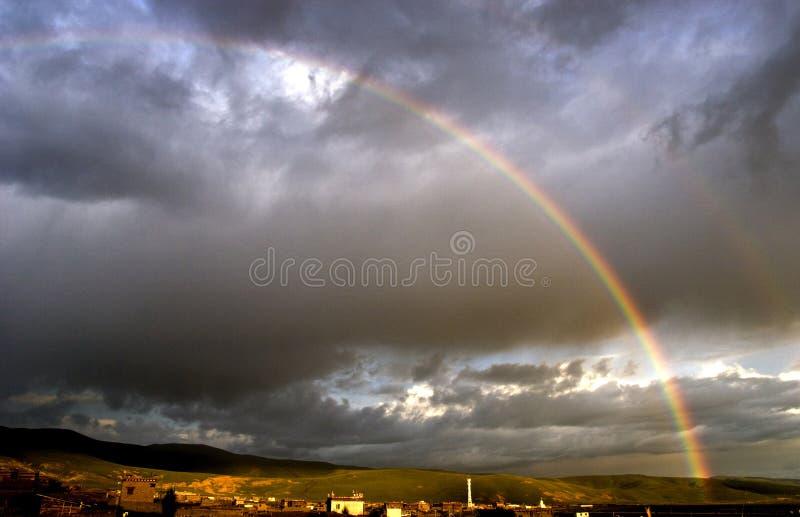 Rainbow in heavy cloud stock photography