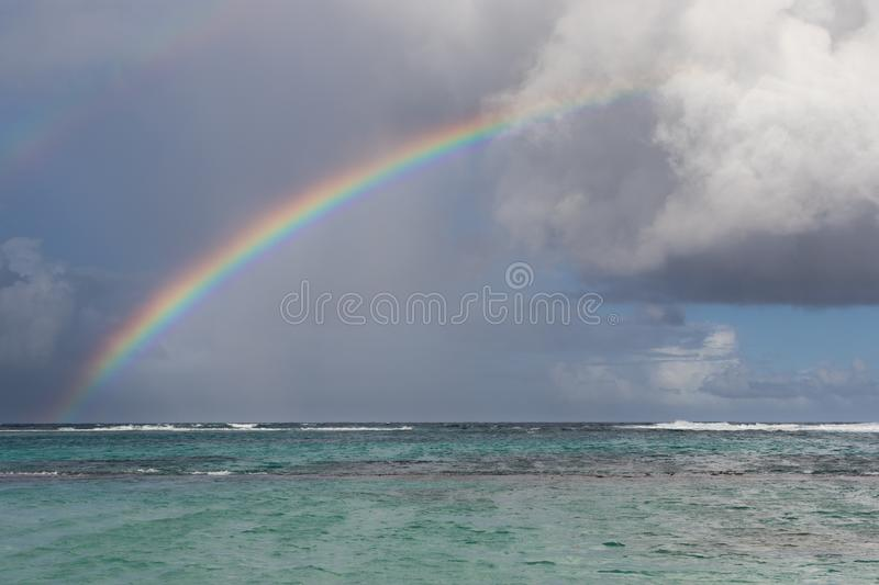 Rainbow, rain and clouds over beautiful cove with turquoise water in Guadeloupe, Caribbean royalty free stock photo