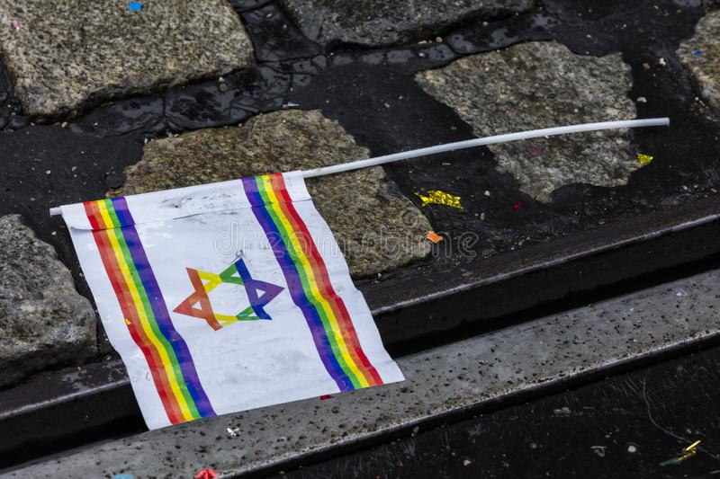 Rainbow israeli flag from the Gay Pride parade also known as Christopher Street Day CSD in Munich, lying on the wet street. Germany stock photo