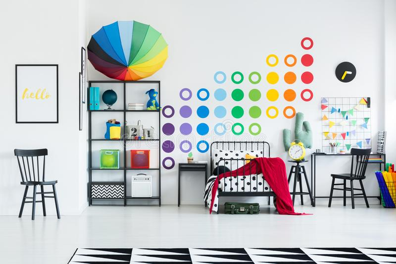 Rainbow kid`s bedroom. With colorful umbrella on black metal rack with toys and boxes royalty free stock photography