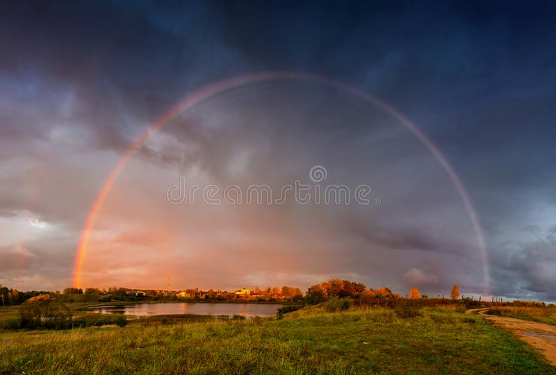 Rainbow landscape and dramatic rain sky stock image