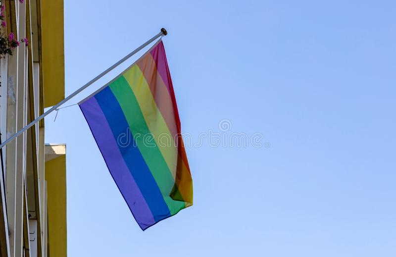 Gay pride flag waving against clear blue sky stock photo