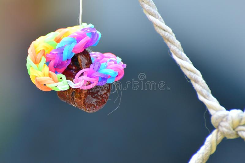 Rainbow loom bracelets on a fishing net. Close-up shot with bokeh background with ceramic mugs hanging on the net royalty free stock images