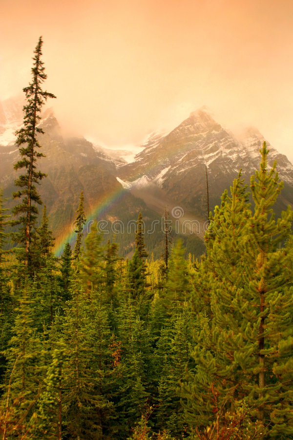 Rainbow in The Mountains. A rainbow illuminates for a brief period with the mountains in the backdrop royalty free stock photo