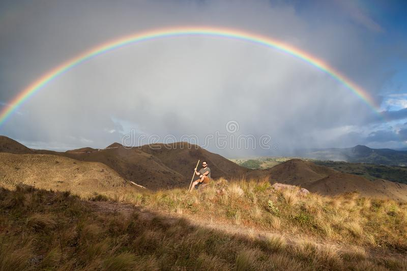 Rainbow in the mountains. Hiker taking time to pose and enjoy the view of a beautiful vivid rainbow on top of the mountains in Canas, Guanacaste Costa Rica stock image
