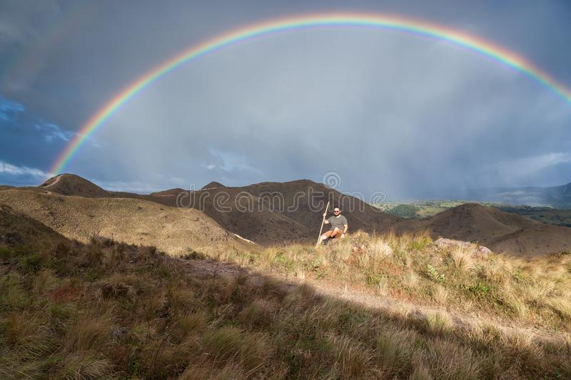 Rainbow in the mountains. Hiker taking time to pose and enjoy the view of a beautiful vivid rainbow on top of the mountains in Canas, Guanacaste Costa Rica stock photos