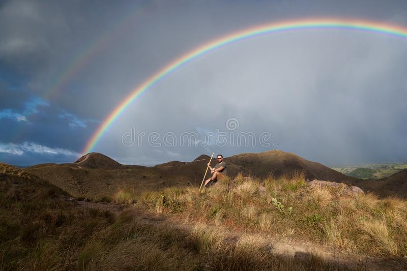 Rainbow in the mountains. Hiker taking time to pose and enjoy the view of a beautiful vivid rainbow on top of the mountains in Canas, Guanacaste Costa Rica stock photography