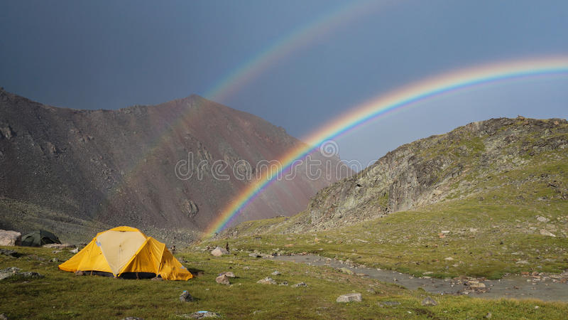 Rainbow in the mountains. Tent against the double rainbow in the mountains stock photo