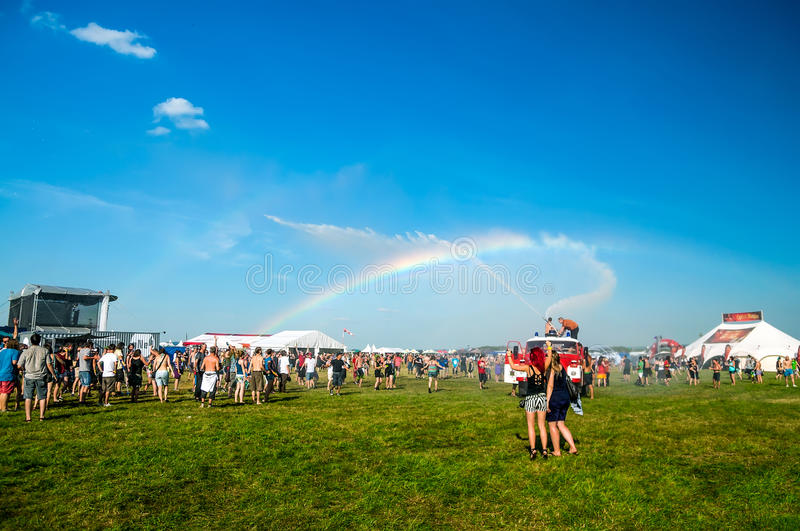 Rainbow in music festival. JULY 2013, People enjoy the rainbow created from a fire truck water at Mighty Sounds festival in Czech Republic, July 2013 royalty free stock photography