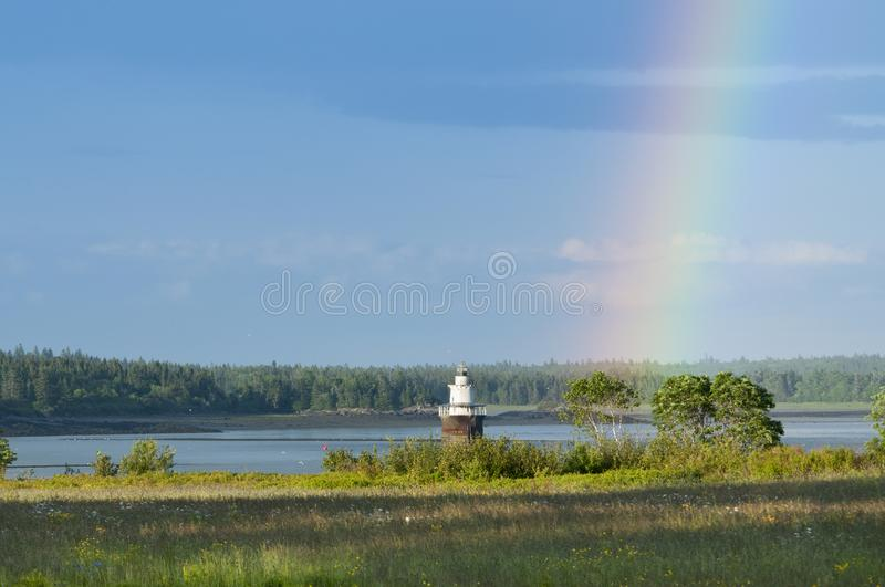 Rainbow Next to Lighthouse in Down East Maine royalty free stock photography