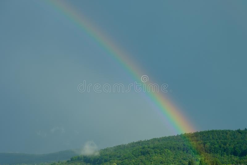 Rainbow ofer a green forest with dark clouds. In the sky stock photography