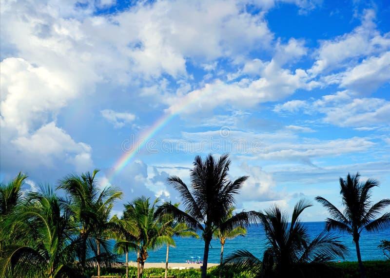 Rainbow off the beach of a resort stock image