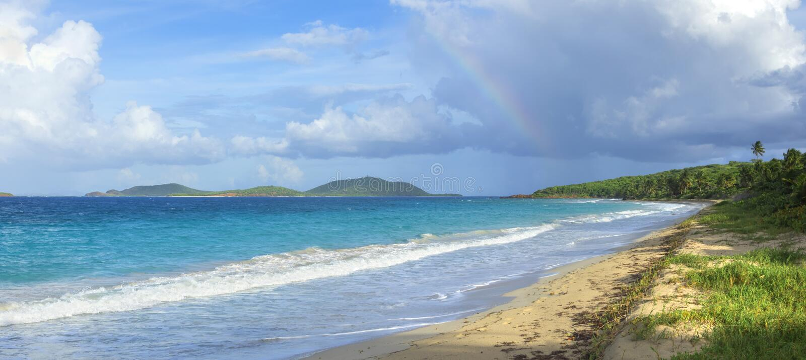 Rainbow over Caribbean island beach. Colorful rainbow in clouds over Culebrita island in panoramic Zoni Beach scene with turquoise blue Caribbean water of Isla royalty free stock photos