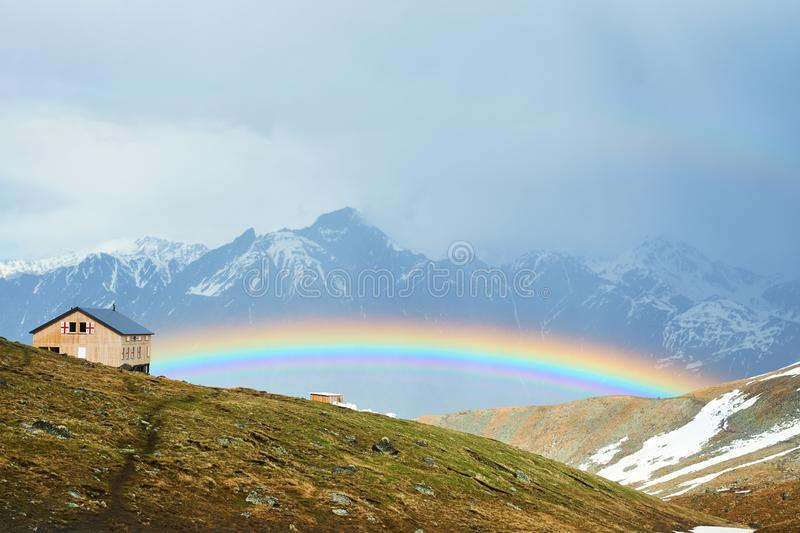 Rainbow over caucasian mountains royalty free stock image
