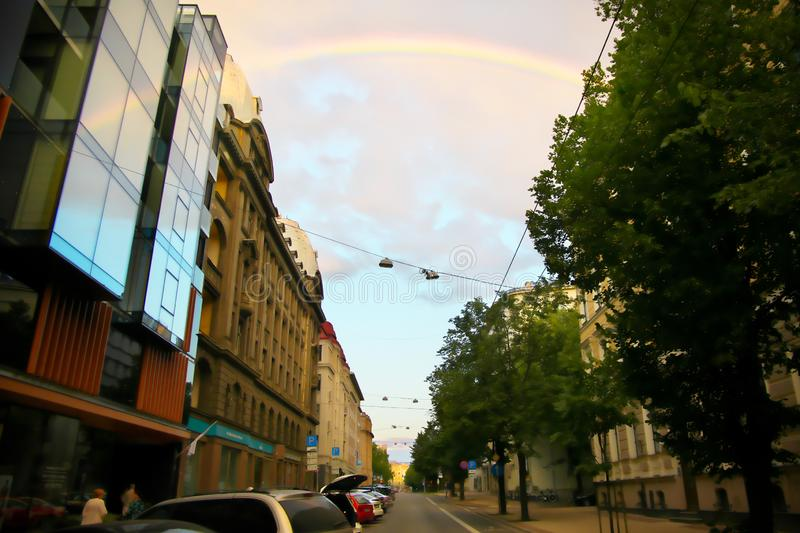 Rainbow over the city street reflecting in the windows of modern office building royalty free stock photo