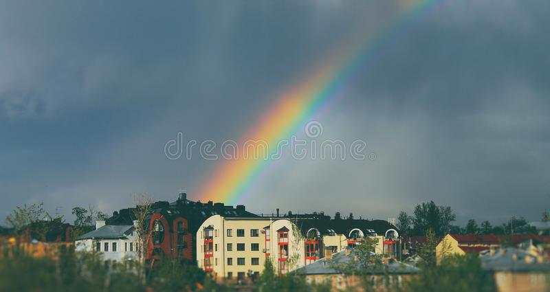 Rainbow over city stock photo