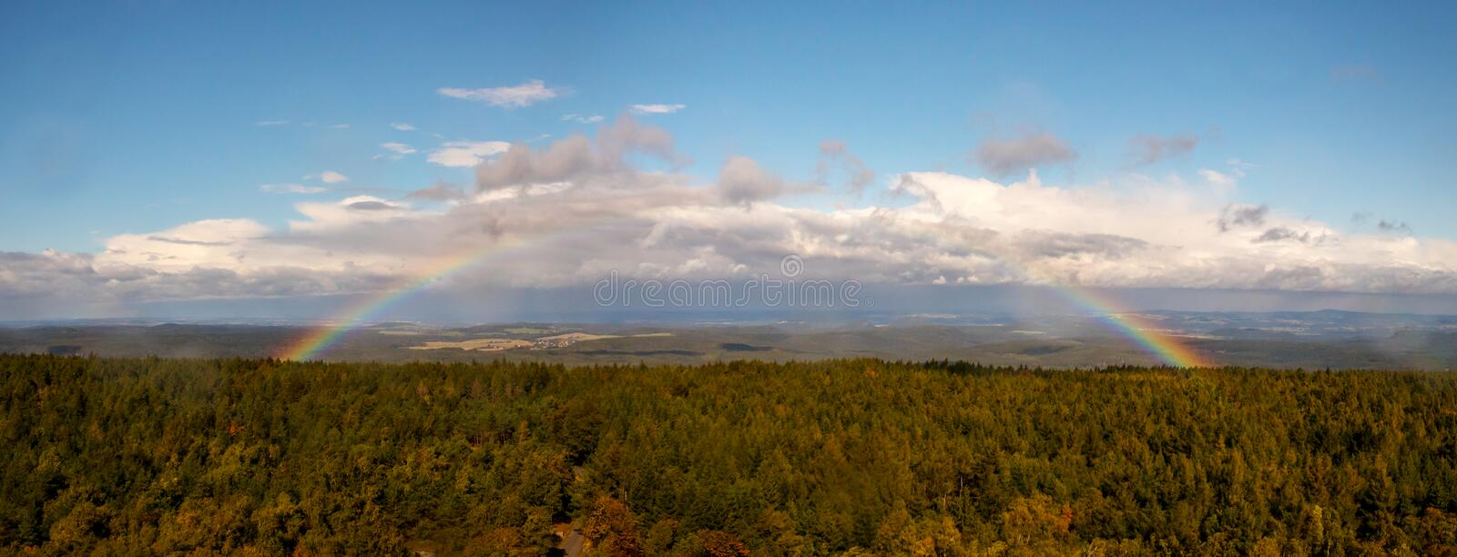 Rainbow over the forest - autumn landscape with rainbow, blue sky and white clouds royalty free stock image
