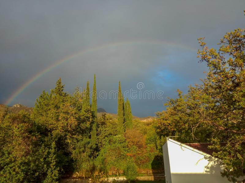 Rainbow over the forest and the old house stock images