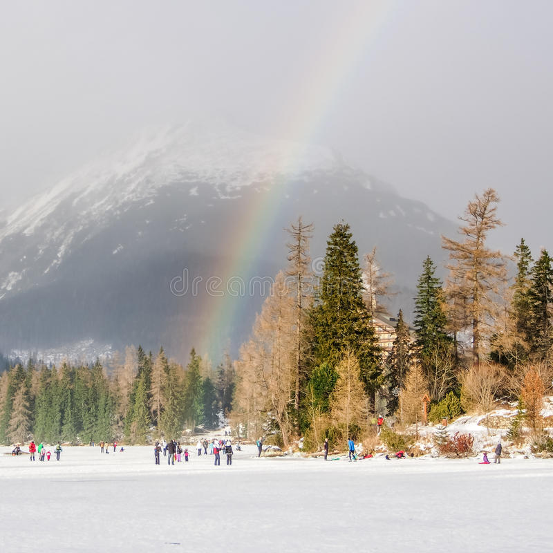 Rainbow over frozen lake in the mountains in winter royalty free stock images