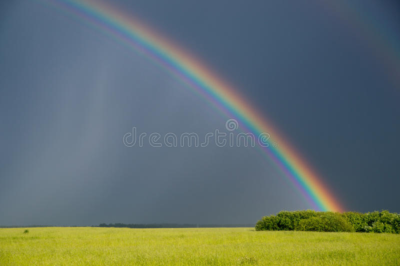 Rainbow over green field royalty free stock photo