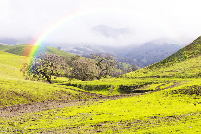 Rainbow Over Green Hills and Meadows in Spring stock photography