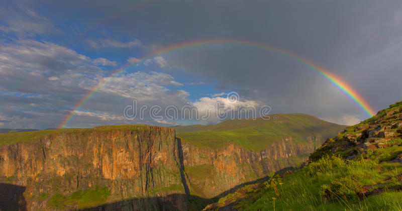 Rainbow over green mountains. In Lesotho stock photos