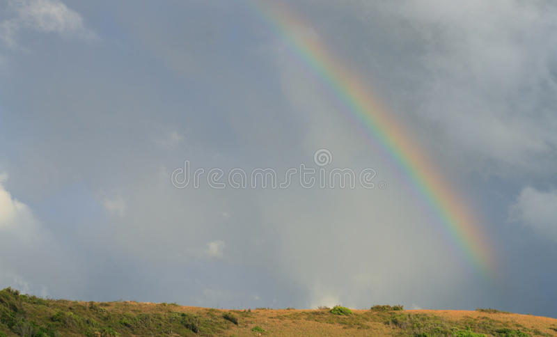 Rainbow over hill with copy space stock images