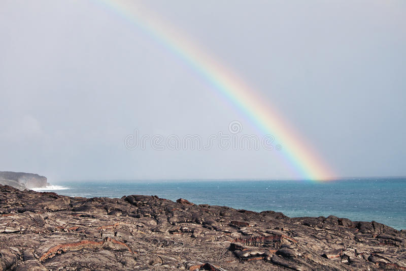 Rainbow over lava flow from erupting volcano. In Hawaii stock photo
