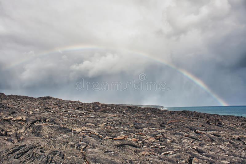 Rainbow over lava flow from erupting volcano. In Hawaii royalty free stock photo