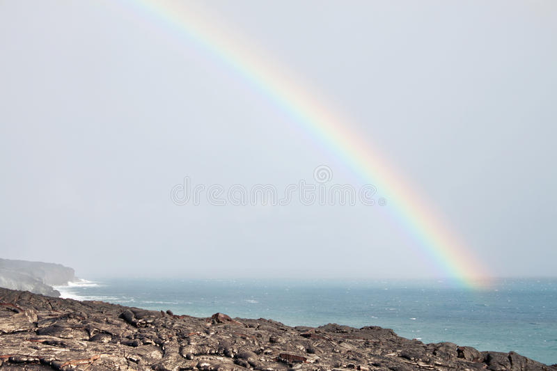Rainbow over lava flow from erupting volcano. In Hawaii royalty free stock image