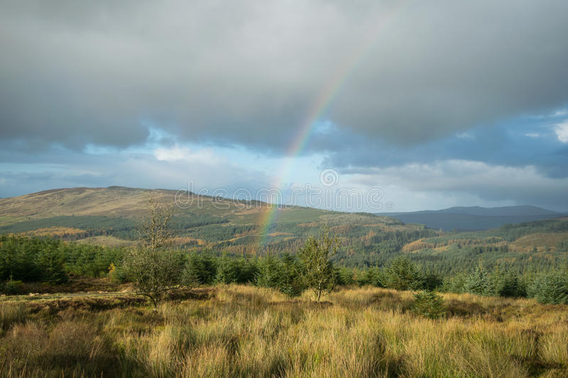 Rainbow over the mountains. Rainbow in the beauty mountains of Gortin Glen park. Northern Ireland. Cloudy Day royalty free stock images