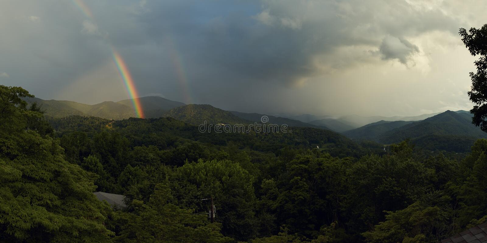 Rainbow over the Mountains. A rainbow over the mountains in Waynesville, North Carolina included in a panoramic stock photo