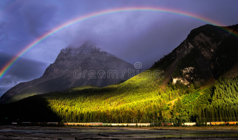 Rainbow over mountains Yoho National Park. Stormy clouds above field town, BC in Yoho nationa park. Golden ray shine through and put a rainbow high in the sky royalty free stock photography