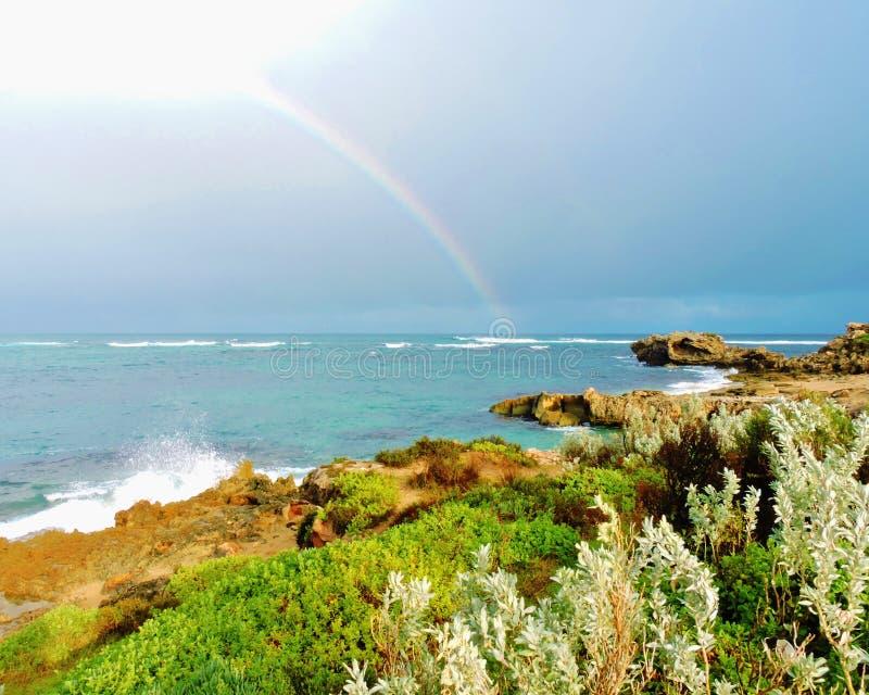 Rainbow over ocean stock images
