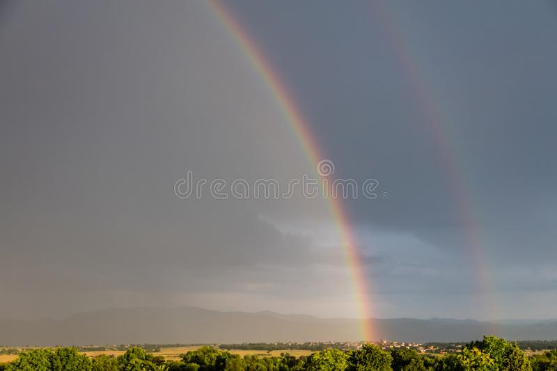 Rainbow over a quaint village and meadows, after the rain, copy space, wallpaper. royalty free stock photo